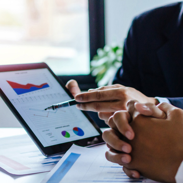 Hands holding an iPad with financial reports